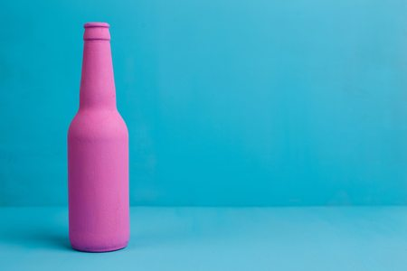 Nice pink beer bottle on blue background. Deceptive attraction o