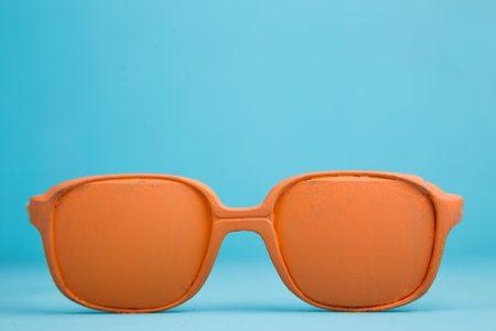 Orange bright pastel eyeglasses on blue background, holiday, spr Zdjęcie Seryjne