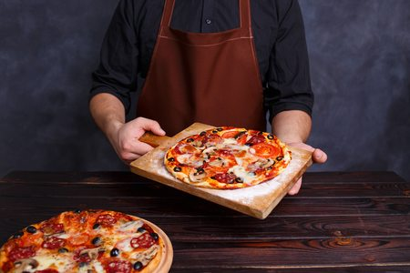 Chef with freshly baked pizza in hands. Cooking process, Italian Archivio Fotografico