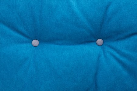 Quilted blue fabric texture of pillow with buttons, close up Stock Photo