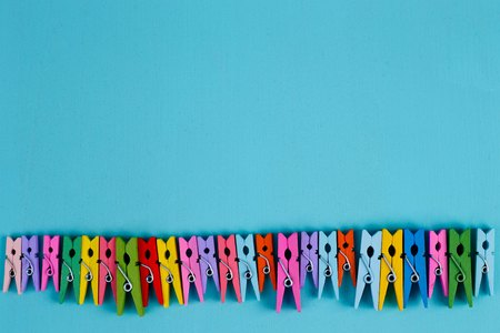 Multicolored bright clothespins on blue background, copy space Stock Photo