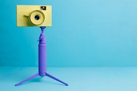 Bright retro vintage camera on tripod on blue background, copy s