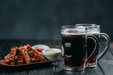 Dark beer and appetizing beer snacks. Table with two mugs of sto Banco de Imagens