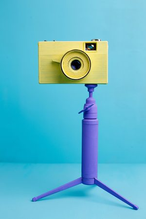 Bright retro vintage camera on tripod on blue background, close