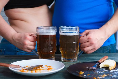 Overweight couple with obese bellies overeating and drinking bee