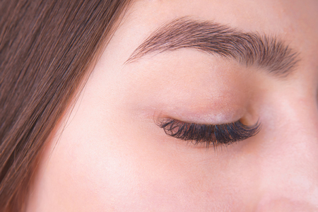 Closed female eye with long eyelashes and beautiful eyebrow, clo
