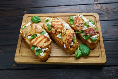 Tasty homemade Italian antipasti bruschettas with grilled chicke