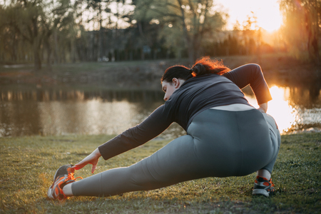 Overweight woman stretching legs doing exercises Stock Photo