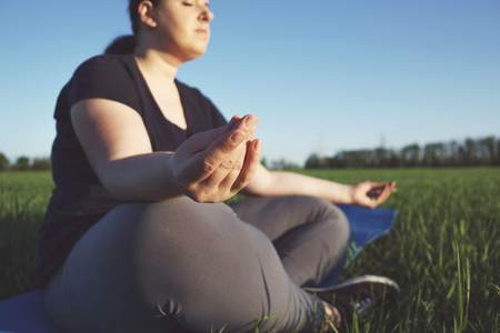 Overweight woman meditating at yoga mat outdoors