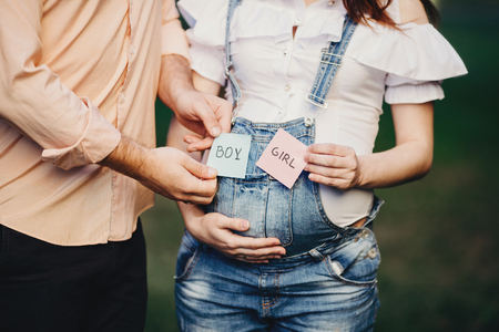 Hands with BOY and GIRL cards pregnant woman belly Banque d'images