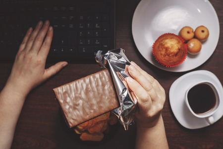Woman eat chocolate and sugary food at workplace