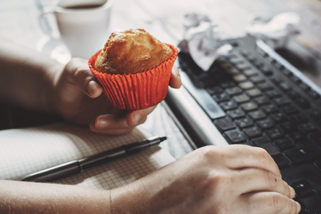 Woman eating muffin at workplace. Unhealthy snack