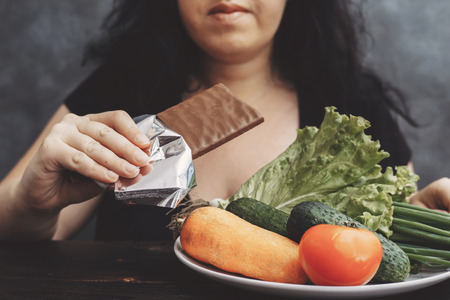 Obese woman eating chocolate refusing healthy food Stok Fotoğraf