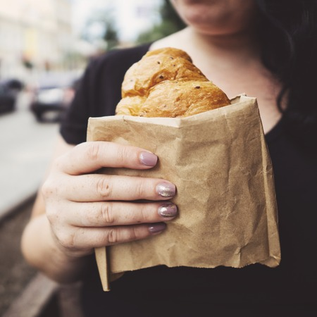 Overweight woman eating croissant at cafe Stok Fotoğraf