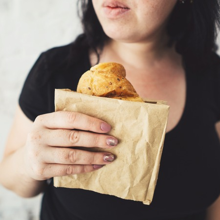 Overweight woman hesitating to eat croissant Stok Fotoğraf
