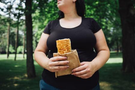 Overweight woman eats doner kebab walking outdoors Stok Fotoğraf