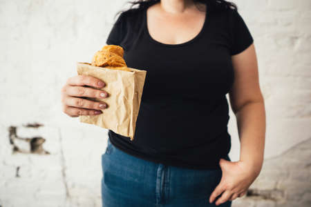 overweight woman with fattening take-out croissant Stok Fotoğraf