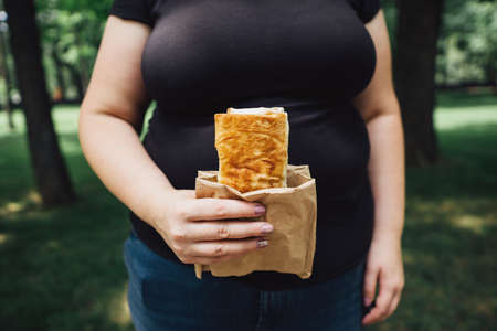 Overweight woman eats burrito walking outdoors Stok Fotoğraf