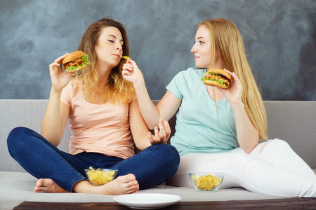 young women sitting at coach eating burgers