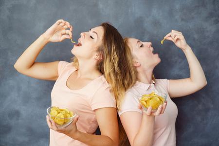 Two cute young women eating potato chips Stok Fotoğraf
