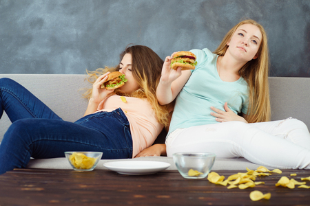 overeaten women sitting with lots of fast-food Stok Fotoğraf