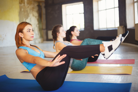 Sporty women doing abdominal crunches at workout