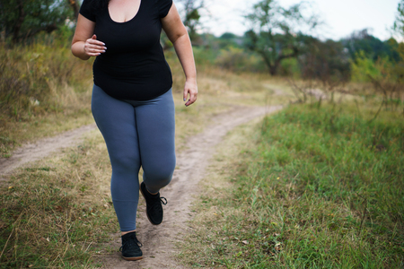 Overweight woman runner go jogging outdoors