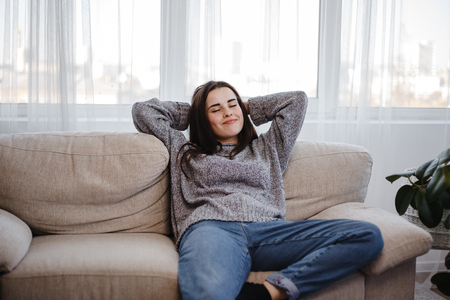 Young woman relaxing on a couch in living room