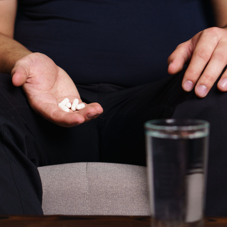 Desperate fat obese man taking pills. weight loss