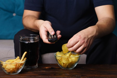 Overweight man with tv remote, junk food and beer Stok Fotoğraf - 112065804