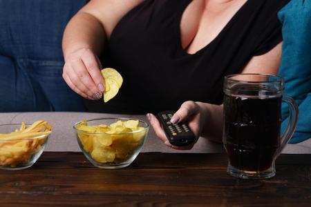 Übergewichtige Frau mit TV-Fernbedienung, Junk Food und Bier be Standard-Bild