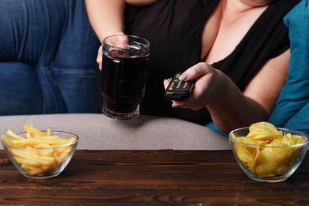 Obese woman with tv remote, junk food and beer Stok Fotoğraf