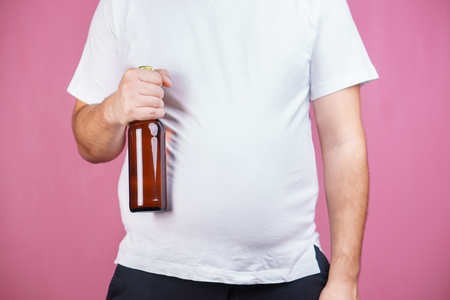 Beer belly, alcoholic addiction. fat man with beer