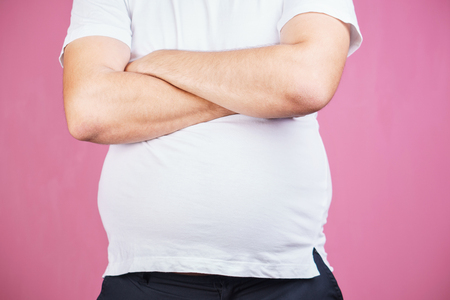 overeating, junk food. obese man with big belly