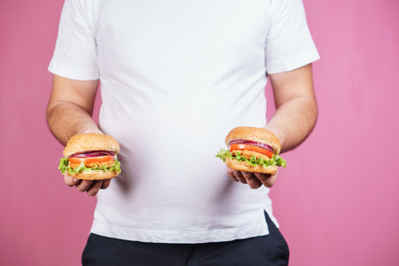 fat man with two burgers. hunger, unhealthy diet