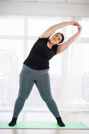 overweight woman exercising at yoga studio Stockfoto