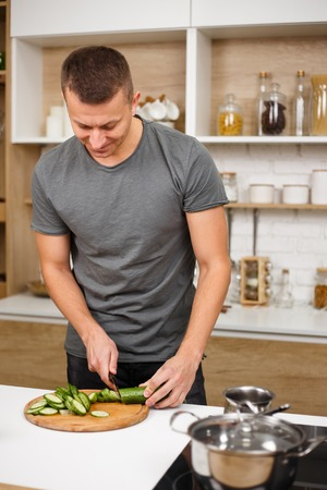 fit muscled man cooking healthy vegetable salad