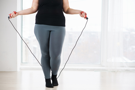 overweight woman with jumping rope before workout