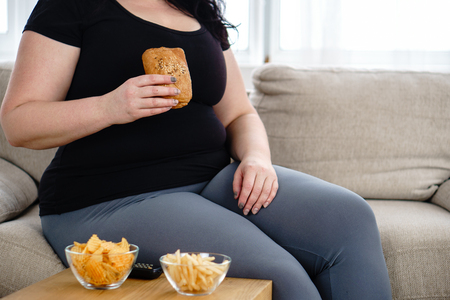 Fat woman watching series at tv eating junk food Stok Fotoğraf