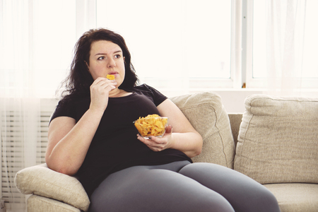 Fat woman overeating junk food.