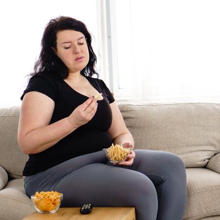 Mujer con sobrepeso con control remoto de tv y comida chatarra Foto de archivo