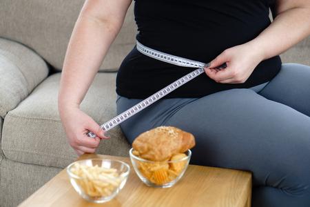 Vrouw met overgewicht meet tailleomtrek