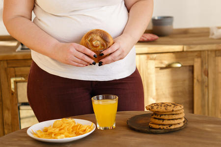 Overweight woman eating sugary foods drinking soda