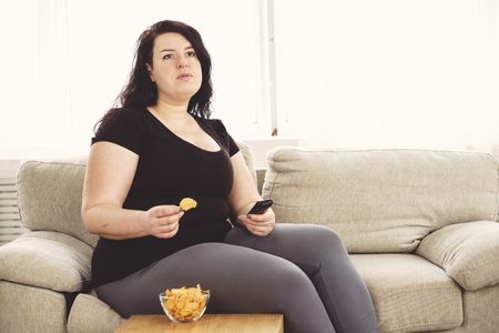 Overweight woman with tv remote and junk food