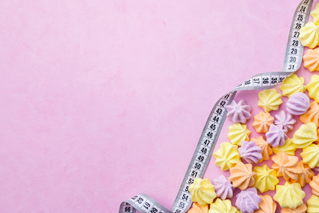 Diet concept meringue cookies and measure tape Banco de Imagens