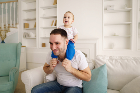 Father giving piggyback his child in living room Stock Photo