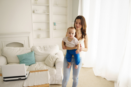 Mother playing with baby boy in living room