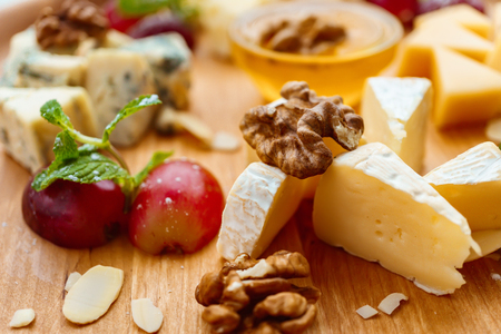 Blue cheese camembert slices with nuts and grapes