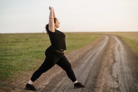 Overweight woman warming up before jogging Standard-Bild