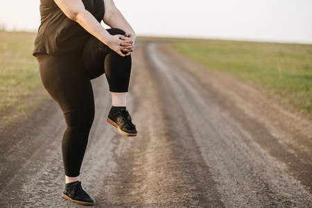 Overweight woman training legs before jogging